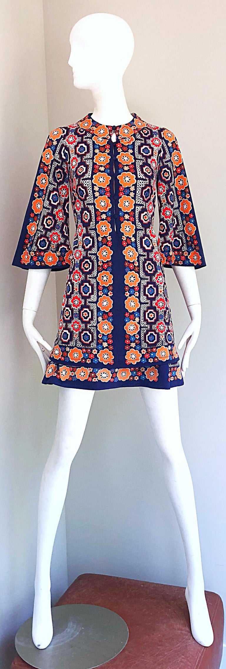 Chic 1960s ARMONIA Italian made jersey tunic and mini skirt ensemble! Features abstract and flower prints throughout in vibrant colors of orange, navy blue, tan, and light blue. Tunic buttons up the front and has dramatic bell sleeves. Mini A-line