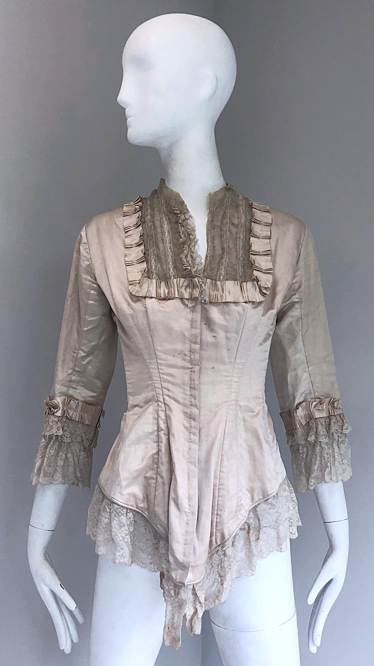 Incredible authentic Victorian Era (approximately 1880s) ivory silk lace corset bustier blouse! Features a fitted boned bodice with  hook-and-eye closures up the front. Puckered silk details around the neck and sleeve cuffs. Layers of matching