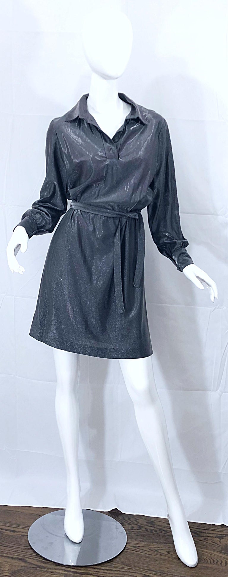 Wonderful 1970s gunmetal metallic long sleeve belted shirt dress! Features a loose fitting bodice that is both comfortable and flattering. Buttons up at neck and at each sleeve cuff. Built in interior elastic waistband stretches to fit an array of