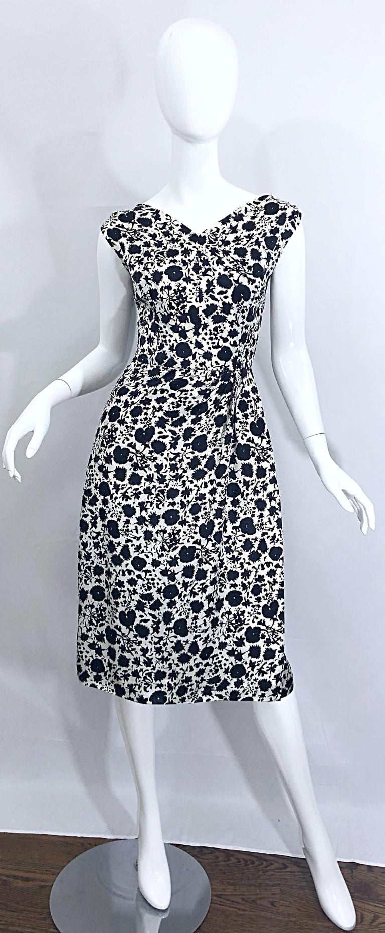 Gorgeous 1950s demi couture HOUSE OF BRANELL black and white floral print silk short sleeve dress! Faux wrap style is flattering and comfortable for an array of sizes. Fitted bodice with a forgivinging skirt. Full metal zipper up the back with