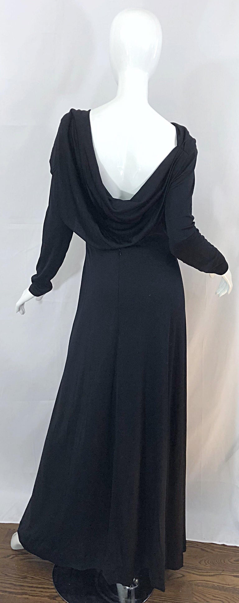 Beautiful 70s ESTEVEZ Couture black long sleeve jersey cape gown! Features a dramatic high neck with a wonderful low-cut draped back that reveals just the right amount of skin. From the side, the dress looks to have a cape. Hidden zipper up the back
