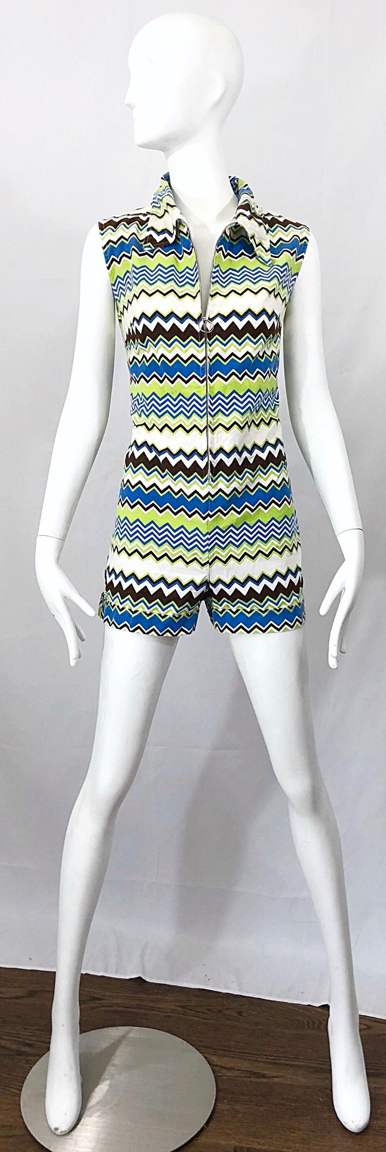 Chic early 1970s one piece romper jumpsuit! Features zig zag prints in lime green, blue, brown and white throughout. Full metal zipper up the front controls cleavage exposure. Nice sturdy cotton fabric keeps shape nicely. Great belted or alone with