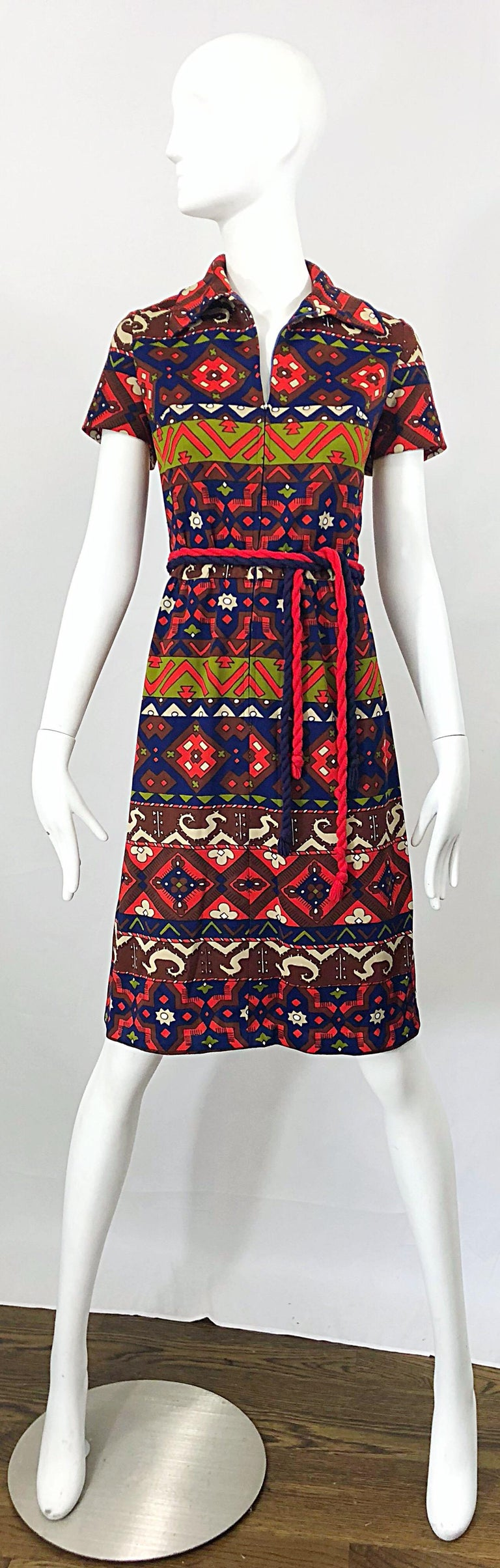 Amazing vintage Aztec inspired 1970s knit belted shirt dress! Features warm tones of red, chartreuse green, navy blue and maroon throughout. Zips up the front to control cleavage. Two tassel belts in red and navy. Great with heels, sandals, wedges,