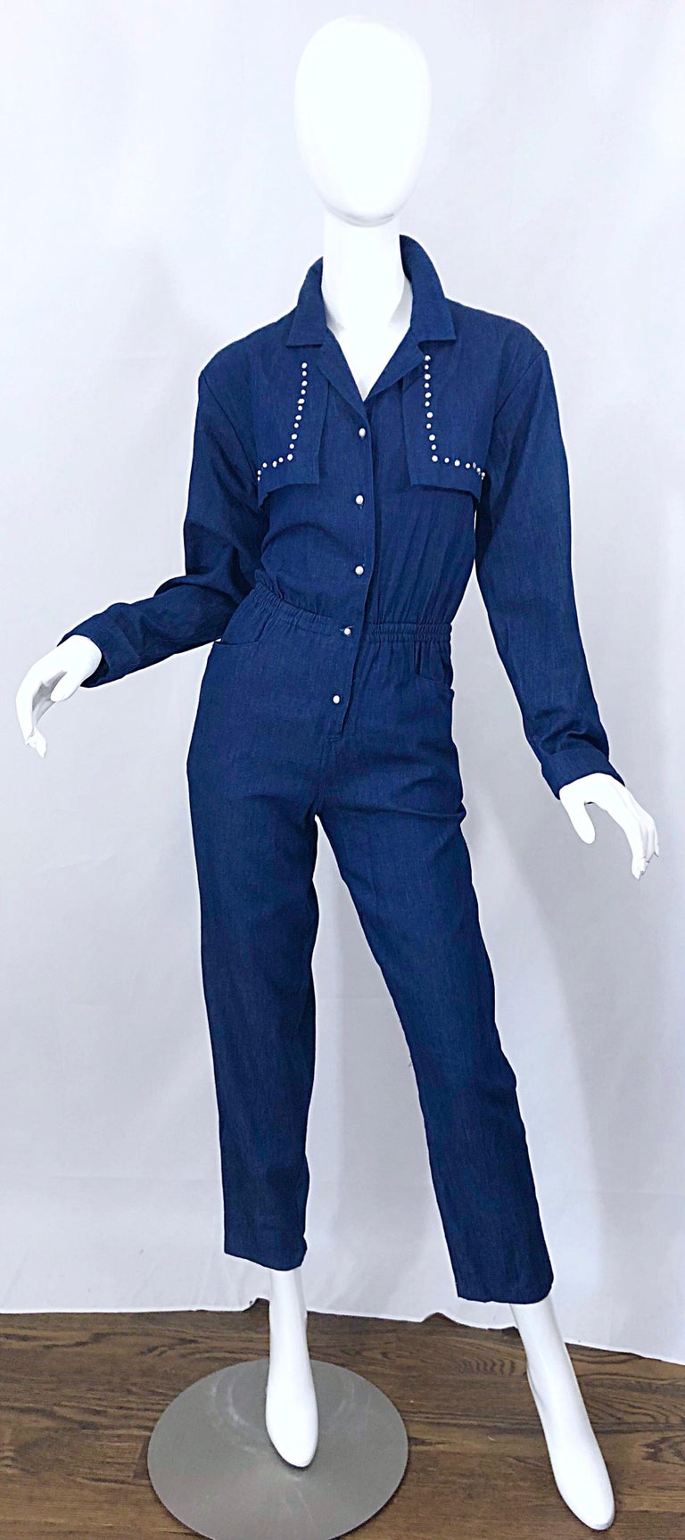 Amazing 90s French Designer (Miss Jett) dark blue denim jean one piece jumpsuit! Encrusted with rhinestones and pearls hand-sewn on the chest lapels, with pearl buttons up the front. Smart tailored bodice with a forgiving elastic waistband. POCKETS