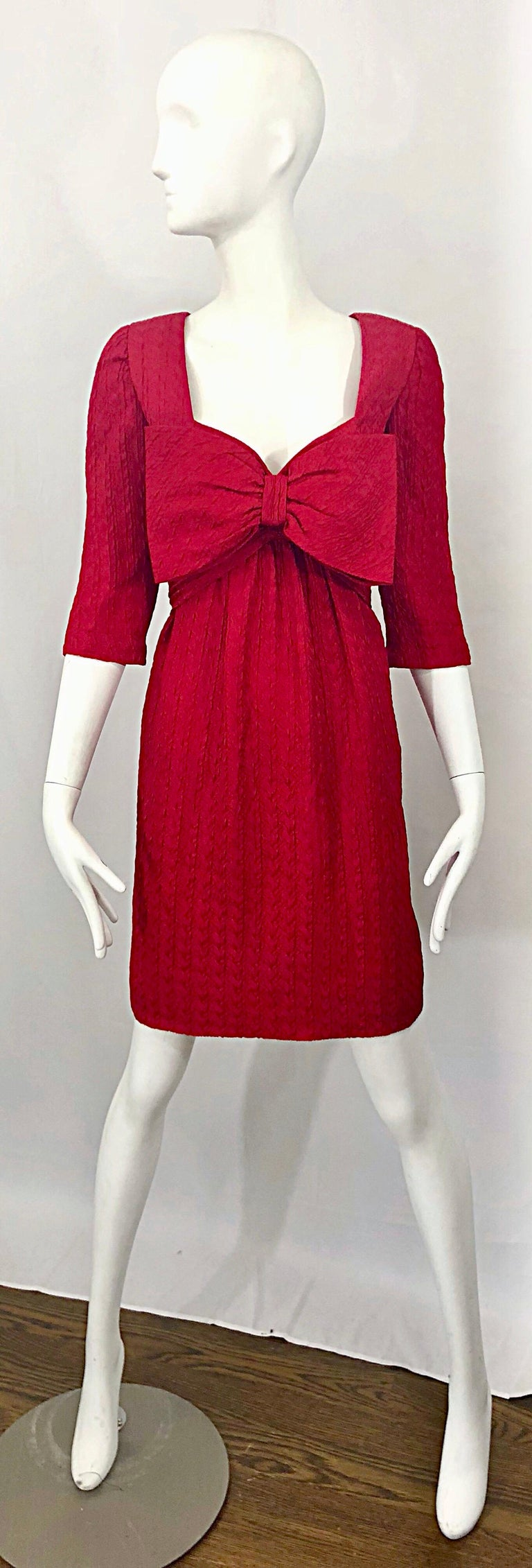 Gorgeous vintage early 90s OSCAR DE LA RENTA lipstick red 3/4 sleeve silk bow dress! Features a sweetheart neckline, with an oversized Avant Garde red bow attached at the bust. Hidden zipper up the back with hook-and-eye closure. 3/4 sleeves hit