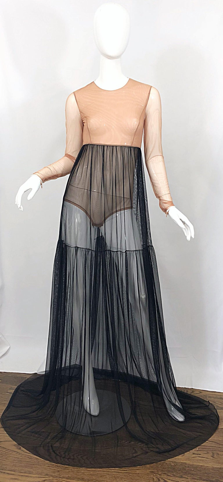 Sexy MICHAEL KORS COLLECTION nude and black sheer bodysuit gown! Features an attached nude bodysuit, with a black high waisted mesh skirt. White trim at neck and sleeves. Hidden zipper at each sleeve cuff. Extra long train adds a dramatic effect,
