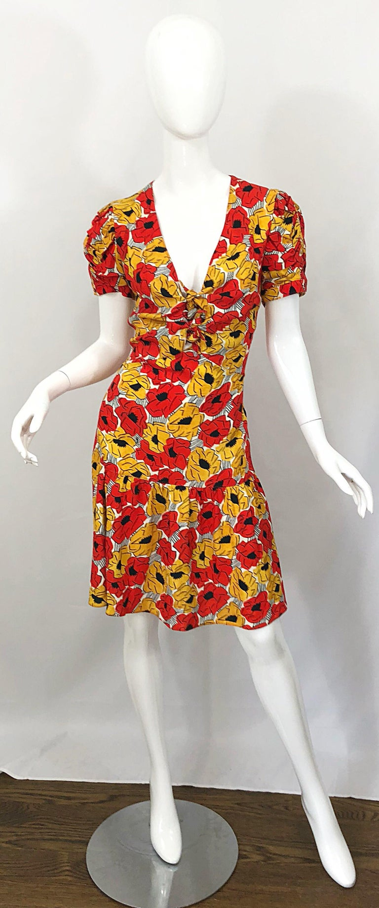 Beautiful YVES SAINT LAURENT red, yellow, black and white poppy print drop waist cut-out dress! Features vibrant colors of red and yellow with black and white throughout. Subtle cut-out details at center bust with ties. Hidden zipper up the side.