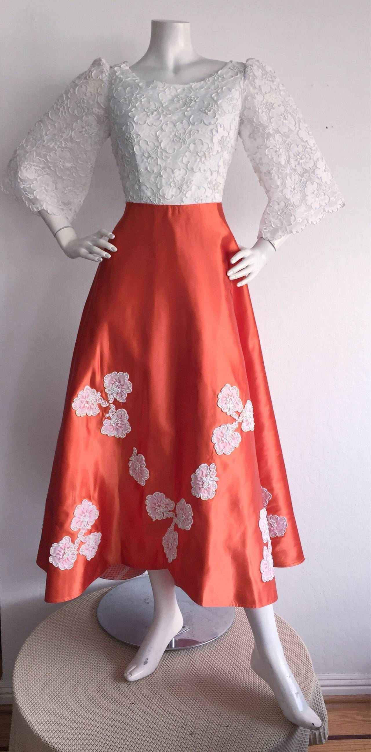 Couture quality! This 1960s beauty is absolutely irresistible, and the workmanship is impeccably done! Hand finished. Gorgeous white crochet/lace bodice, with full bell sleeves. Beautiful vivid orange full satin skirt, with a horsehair sewn attached