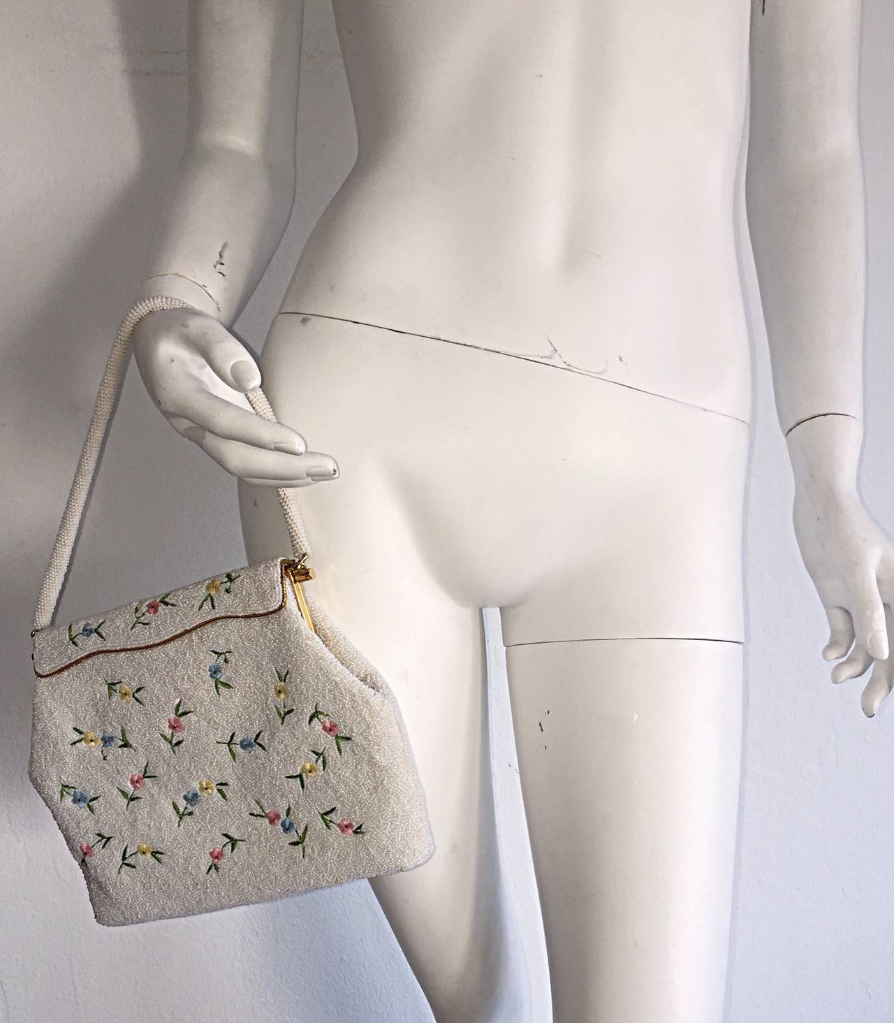 Featuring a gorgeous 1960s fully beaded purse! Pastel colored beaded flowers throughout, with a gold trimmed flap closure. Fully lined, with multiple pockets to fit modern day accessories (ie-iPhone, Android, cosmetics, etc.) The perfect size! Can