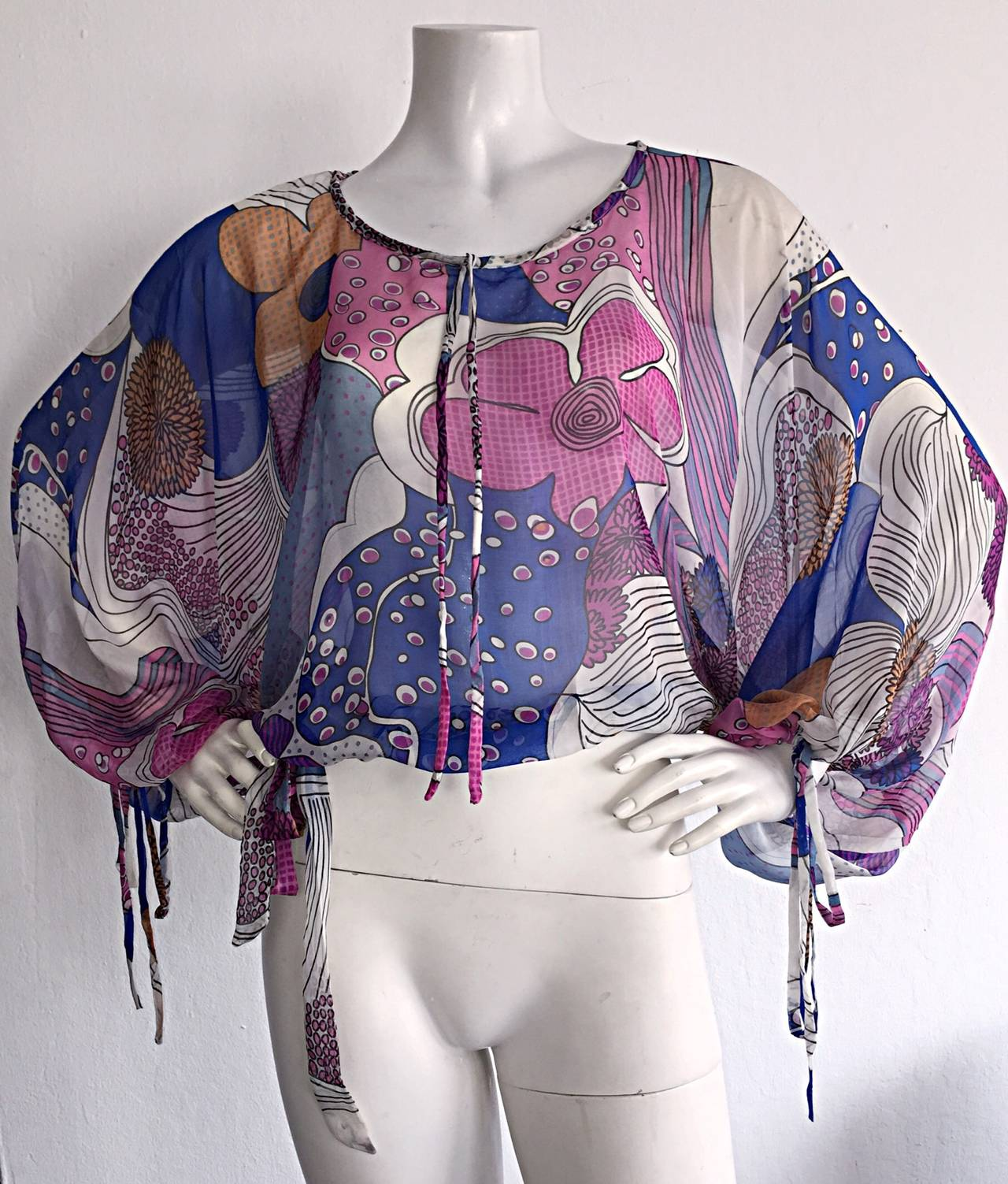 Incredible vintage Kenzo Bohemian blouse! Can be worn so many different ways! Billow sleeves, with a loose fit, and drawstring waist, to fit many sizes. Wild flower print throughout. Ties at sleeves, neck, and waist. Can easily transition from day