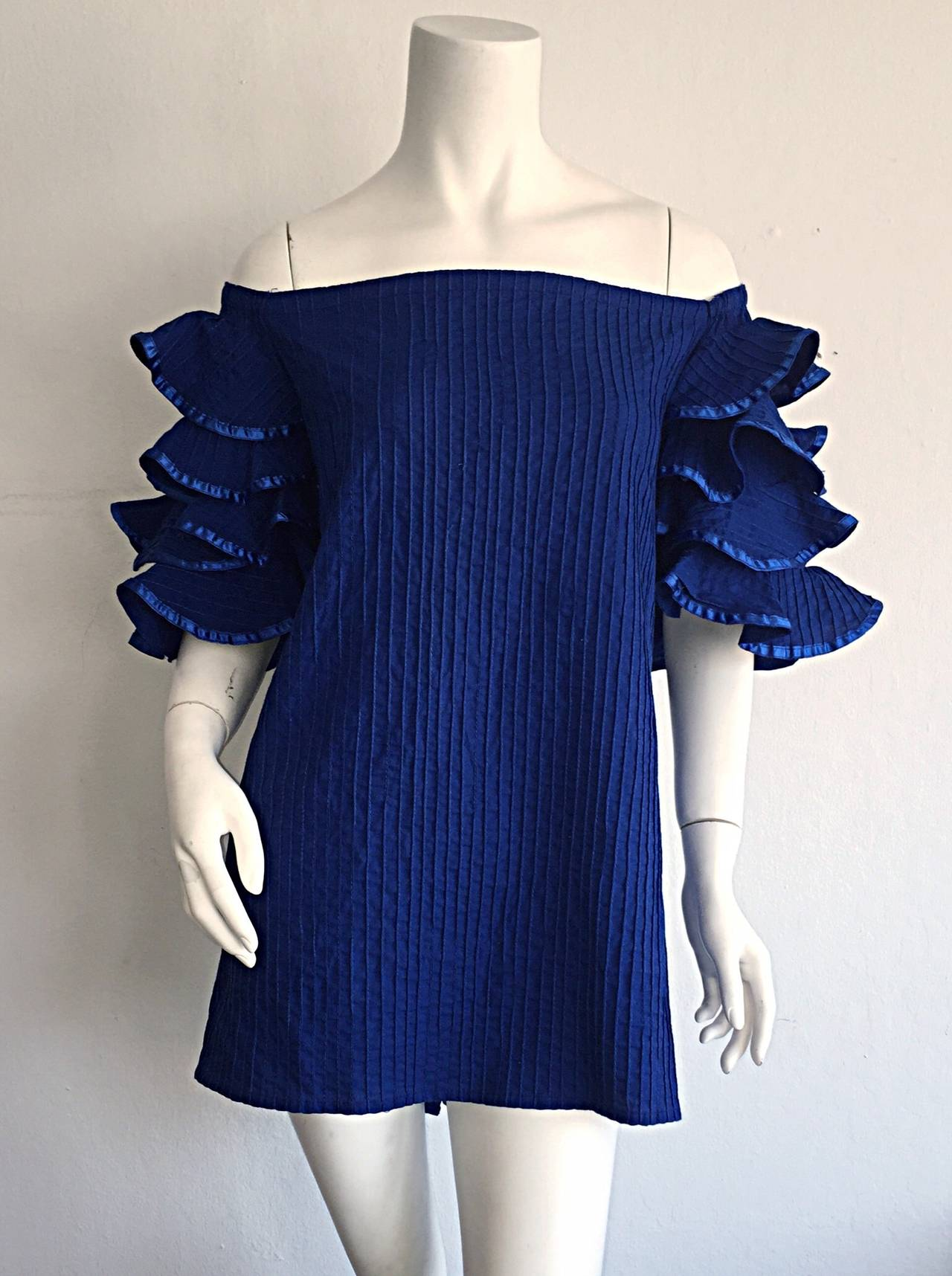 Absolutely beautiful vintage Tachi Castillo cotton blouse! VIbrant blue color, with ruffle sleeves. Buttons up the back. Can be worn on, or off the shoulders. Looks great alone, or belted. Perfect with shorts, jeans or a skirt. In great condition.