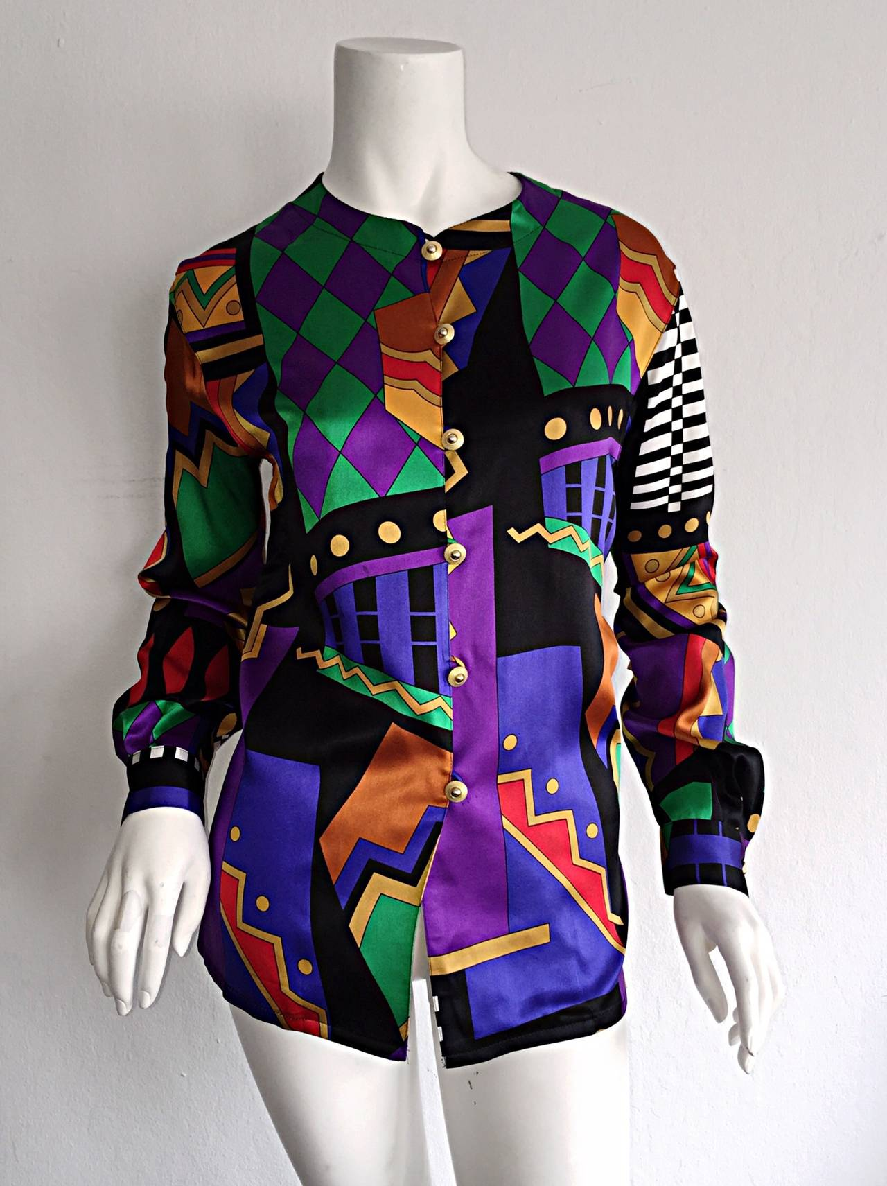 Simply irresistible vintage Louis Feraud silk blouse! Wonderful colors, with amazing geometric prints throughout! Amazing fit! Gold buttons up the bodice, and at each cuff. Can be worn a number of ways--buttoned all the way up, top buttons left