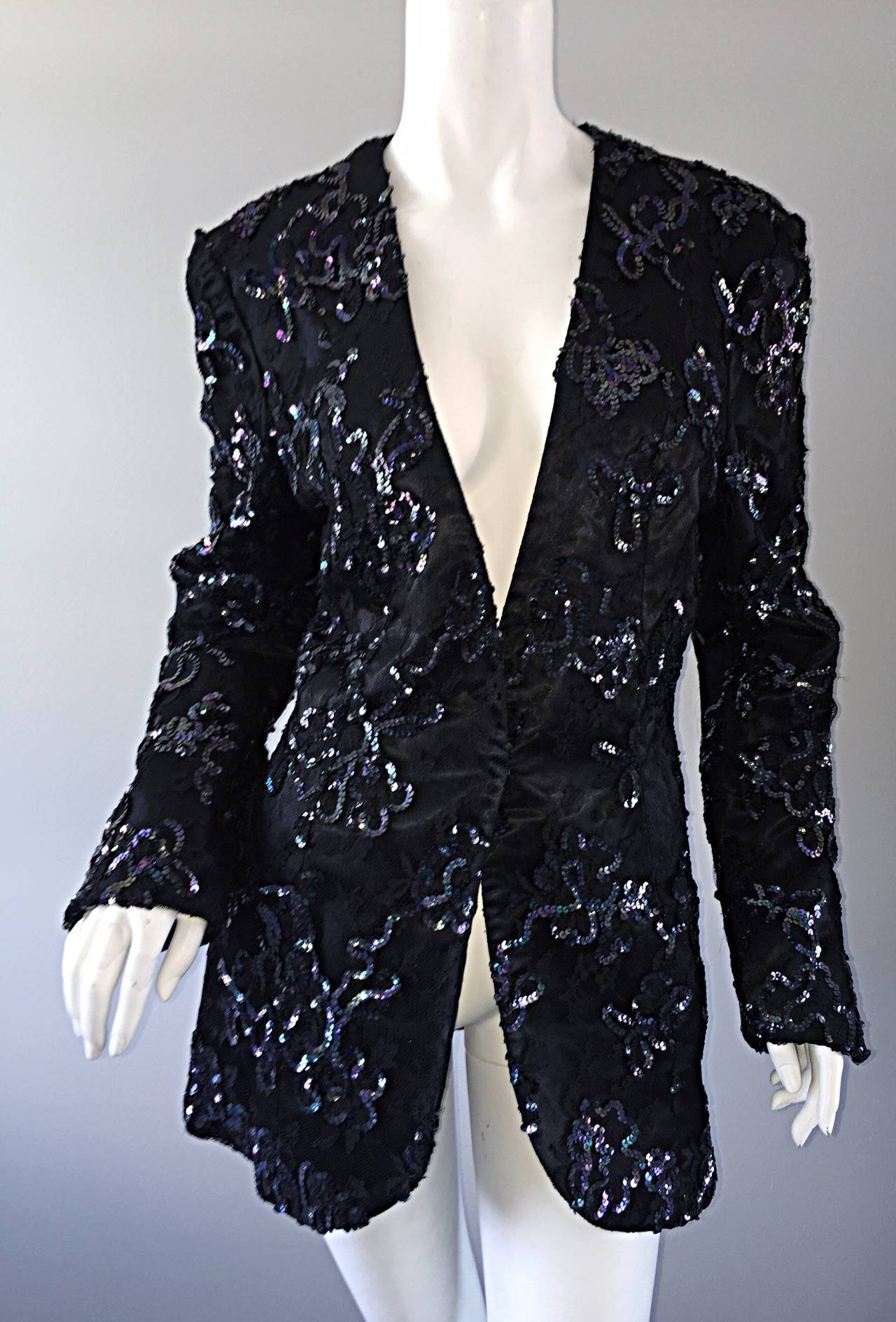 The ULTIMATE black blazer, by Joanna Mastroianni! Black silk, with black french lace overlay, adorned with iridescent sequins throughout. Looks great with denim, trousers, a skirt, or simply over a dress. Single hook-and-eye closure at waist. Fully