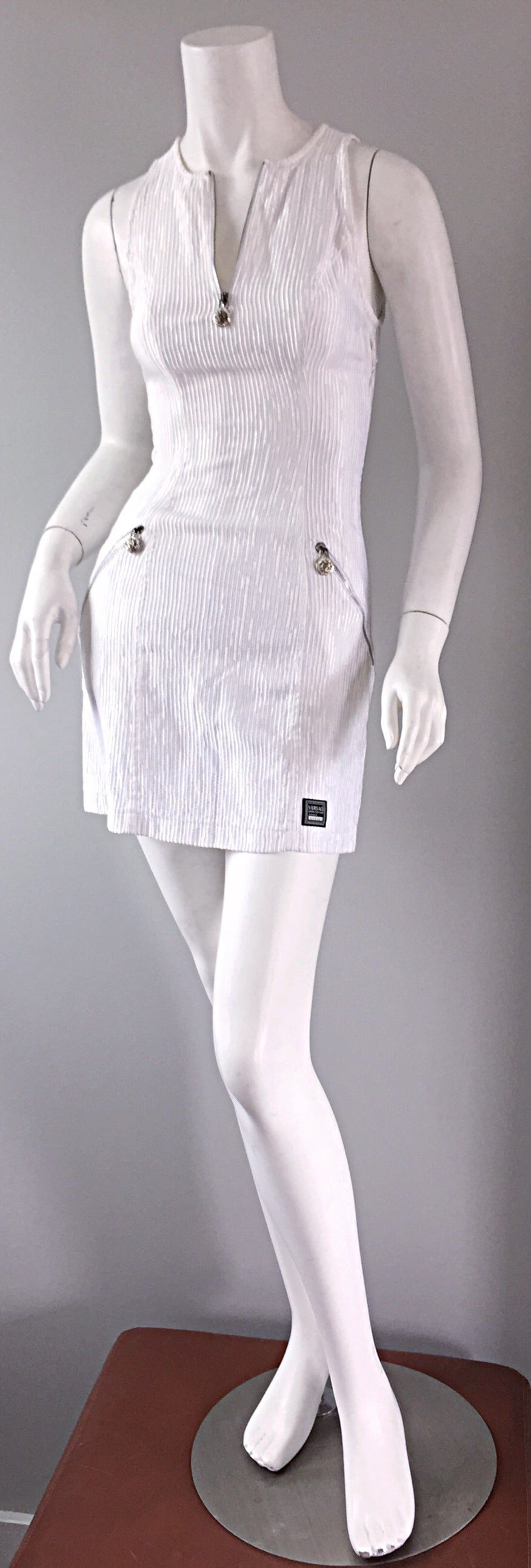 The ultimate vintage Gianni Versace pre-death bodycon dress! Stark white color, featuring Medusa zippers, encrusted with rhinestones. Ribbed detail, with a 'scuba' fit. Extremely flattering, with the option to wear the dress zipped up, or left open.