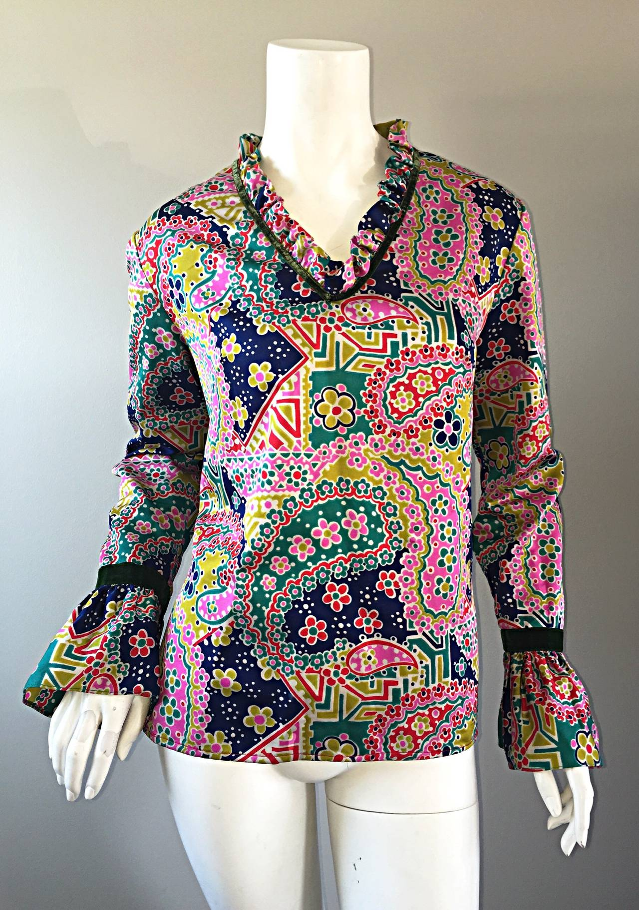 Awesome vintage 1970s top! Features colorful prints of paisley and florals throughout. Wonderful poet's sleeve, with green velvet ribbon detail at cuffs and neck. Ruffles at the neck. Hidden zipper up the back. Looks great alone, or perfect with a
