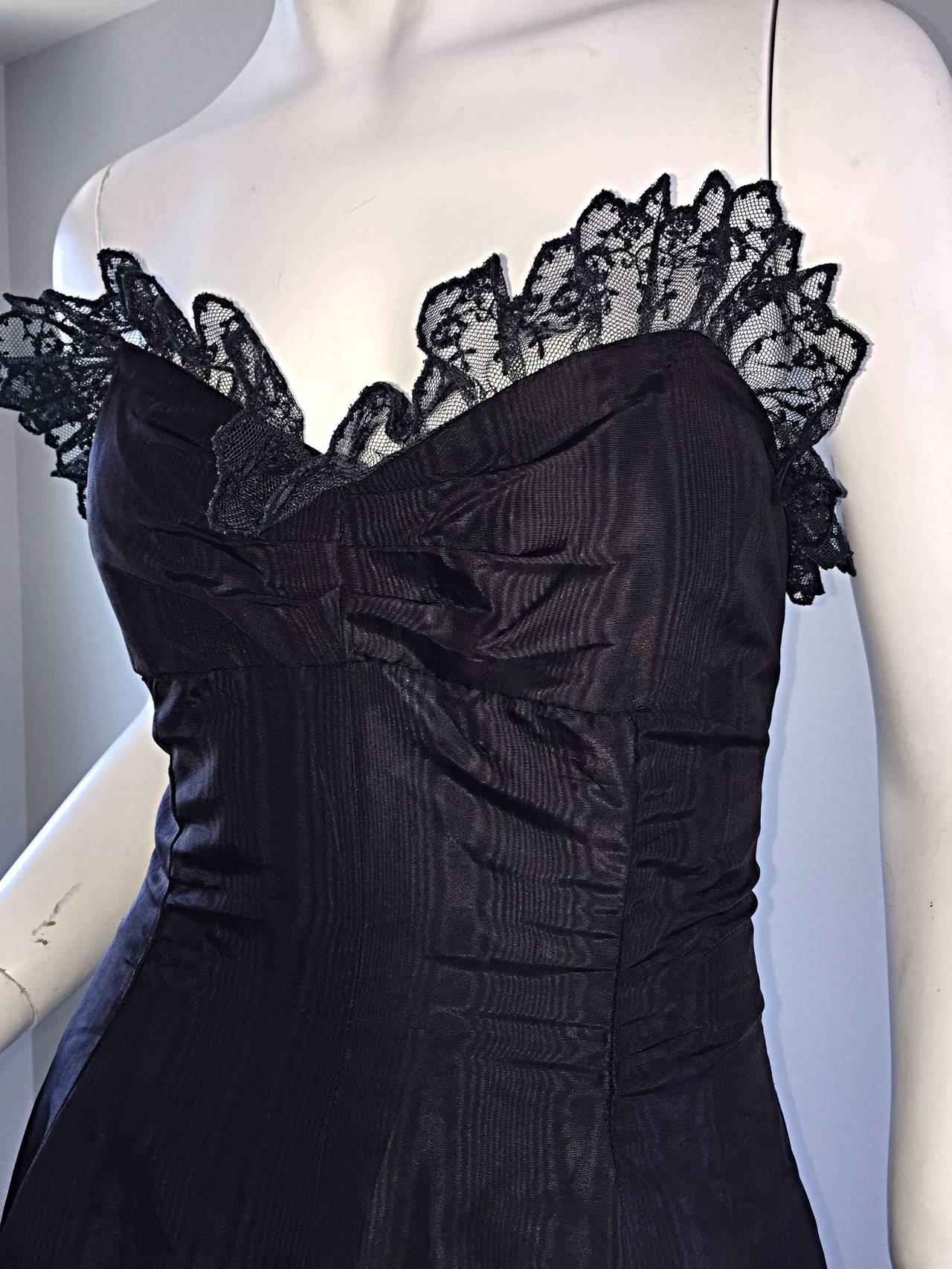 Gorgeous 1950s strapless silk taffeta dress! Jet black color, with black lace accents at bust. Couture quality workmanship, with a built in underdress to help hold the dress up, and boning on interior bust. Full skirt, with plenty of room to add