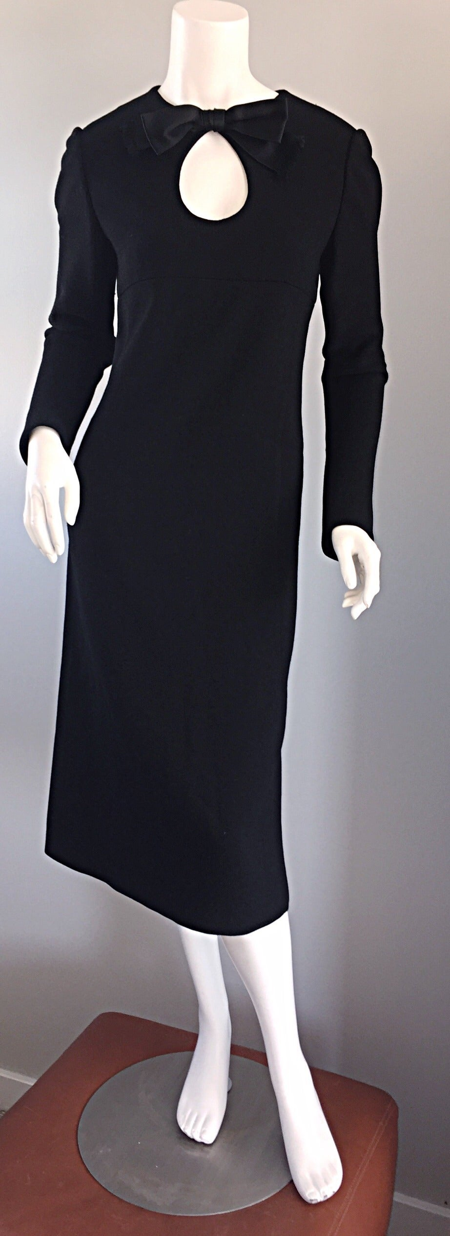 Iconic and rare! 1960s Pierre Carding black wool midi dress! A sleek design, witha  slight A-Line fit that looks incredible on the body! Chic cut-out above bust, adorned with a silk bow. Tailored long sleeves. A classic, yet stylish staple for any