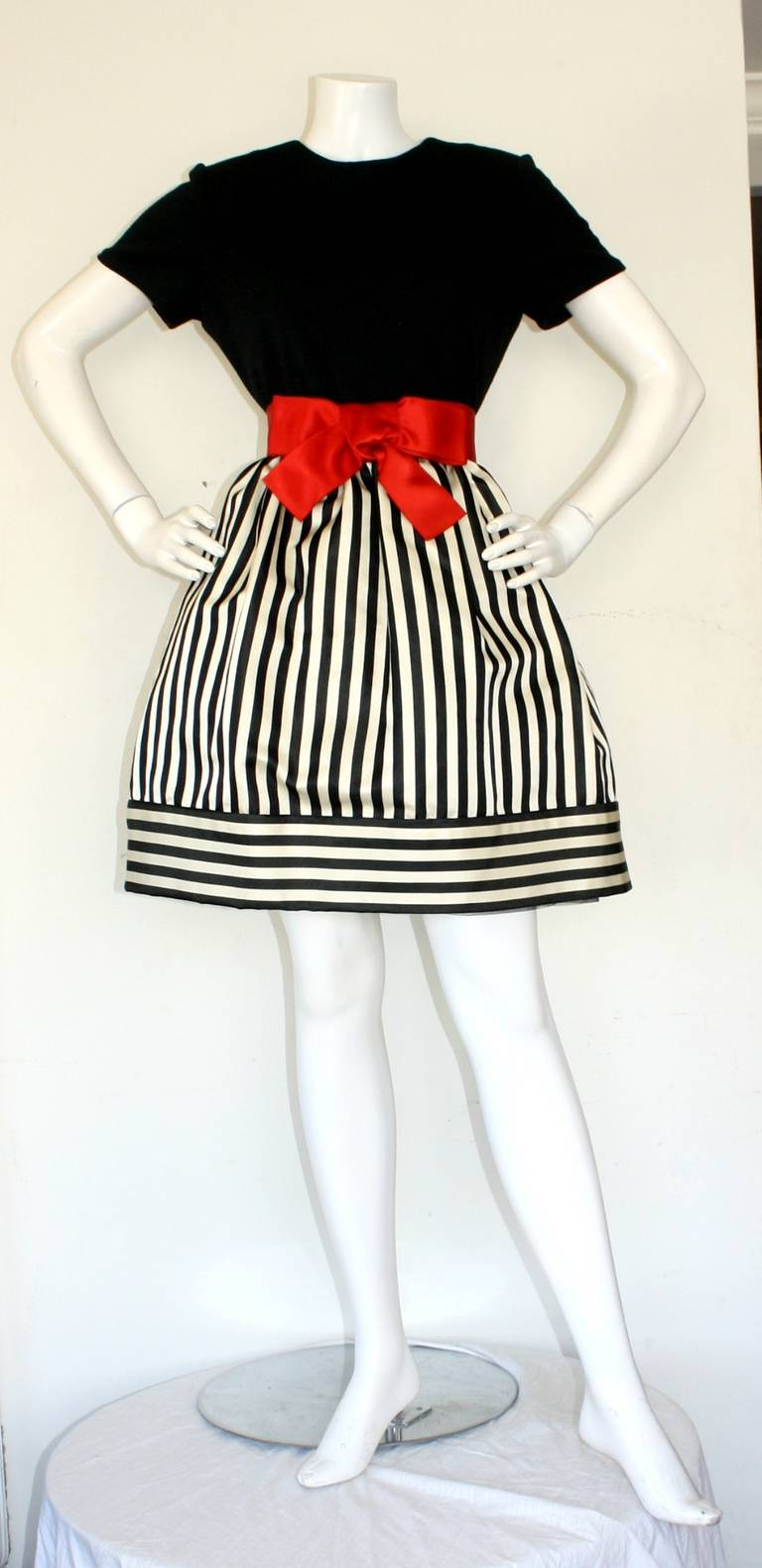 Featuring the cutest vintage Bill Blass dress! Built in crinoline, under a chic black and white silk skirt. Attached red silk bow belt, with a fitted black bodice. In great condition. Approximately Size Small-Medium  Measurements: 38 inch