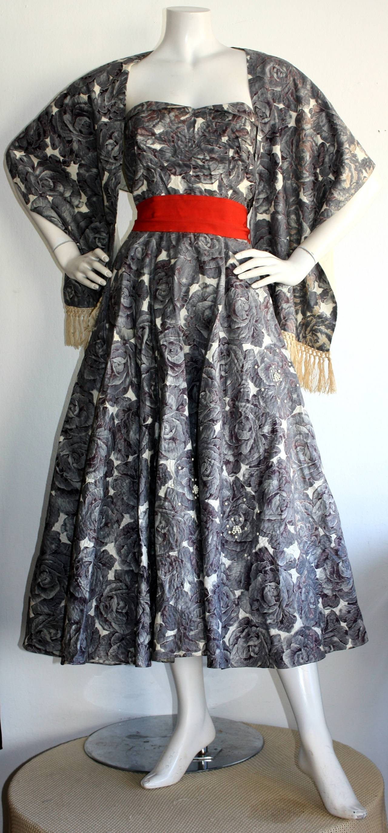 Incredible vintage Fred Perlberg dress and fringed shawl. Beautiful grey  and white rose print, with attached bright red belt. Shelf bust, with white opaque beads throughout the skirt. Attached crinoline. In great condition. Approximately Size