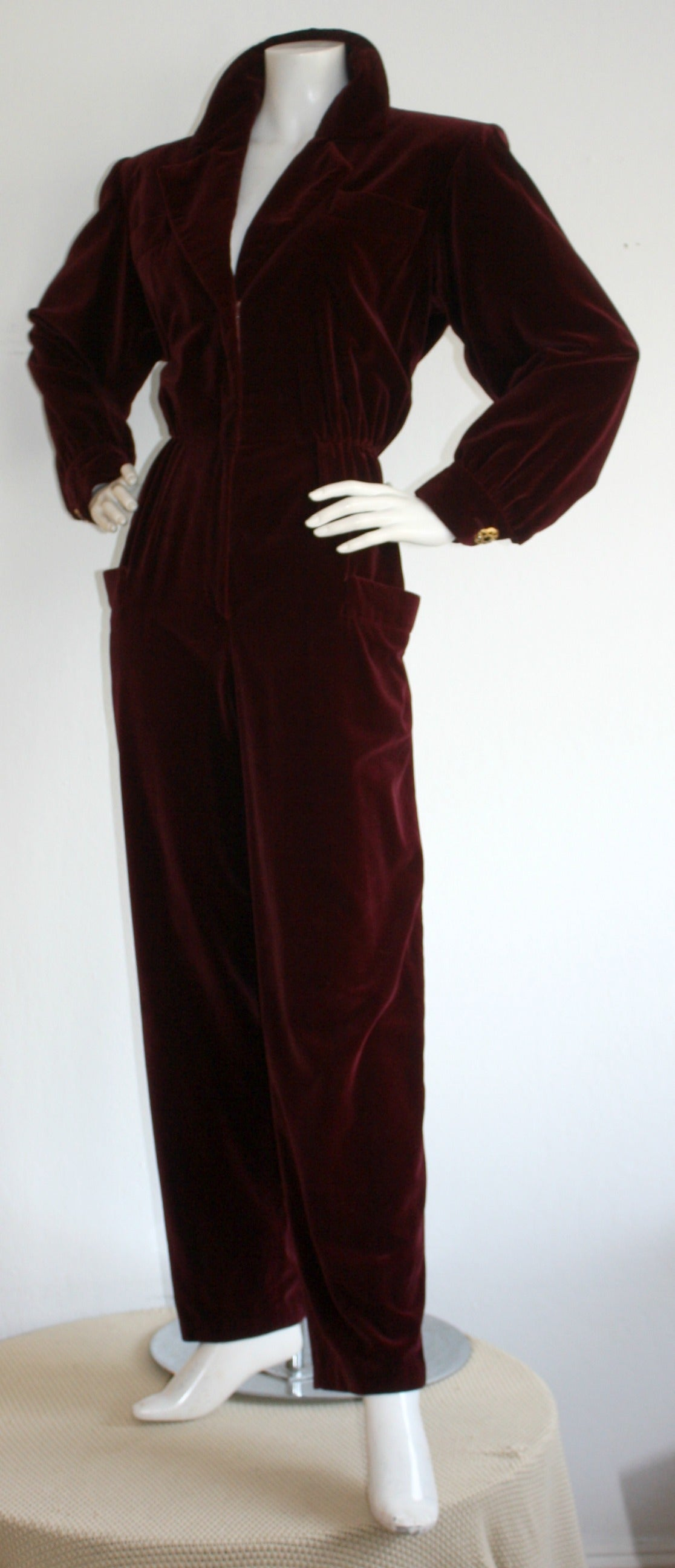 Very important, Iconic, vintage Yves Saint Laurent burgundy velvet jumpsuit! Softest silk velvet, with a pocket at each hip. Features intricate gold buttons at each cuff. Zips up the bodice to control cleavage level. A beautiful piece, that looks
