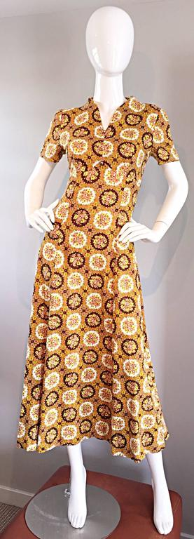Cute 1970s JOSEPH MAGNIN cotton midi dress! Features gorgeous warm tones of orange, brown, yellow and green throughout, mixed with tiny medallion flower prints. Two gold balls at bust. Flattering v-neck, with a full skirt. Hidden zipper up the back.