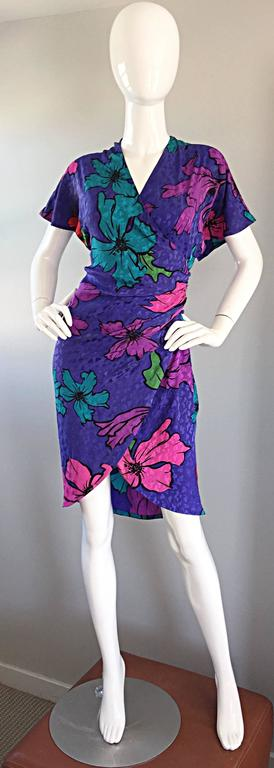 The perfect little spring or summer dress by FLORA KUNG! Wrap style, with short dolman sleeves (which can accomodate a variety of bust sizes). Interior ties, and silk covered buttons up the side bodice. Vibrant purple background, with pink, fuchsia,