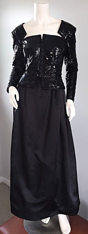 Gorgeous vintage TRAVILLA black gown! Features an all-over sequined bodice, with avant Garde cut-outs, trimmed in black satin at the bust. Looks like a strapless dress with gloves. Mock jeweled buttons up the bodice, with a nipped wasp waist. Full