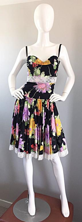 Such a pretty cotton sundress from TRACY FEITH! Black lightweight cotton with multi-colored floral prints throughout. White lace detail at bust, waist, and at the hem. Full skirt, with an ode to the 1950s / 50s. Extremely well made, with a