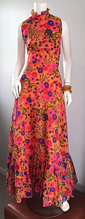 Amazing 70s colorful psychedelic chiffon maxi dress! Features a vibrant floral print in orange, pink, blue, green, red and purple! Chic ruffled neck, and ruffle hem. Peek-a-boo back with buttons at top back neck. Full metal zipper up the back.