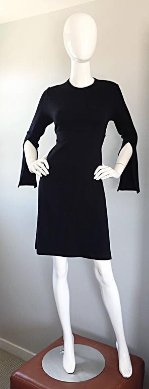 The perfect little black dress by MORGANE LE FAY, but with an awesome twist! Features 'slashed' sleeves for a slight Avant Garde look! Expertly constructed with a heavy eye to detail and construction. Wonderful tailored fit with an attached tie belt