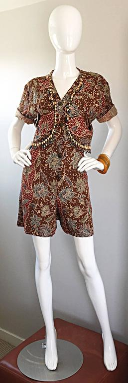 Incredible vintage onesie / romper! Lightweight cotton and rayon blend with tribal ethnic prints throughout. Embellished with hand-sewn beads and bells on the bodice. Attached vest features crochet cut-outs at each side. Hidden zipper up the front