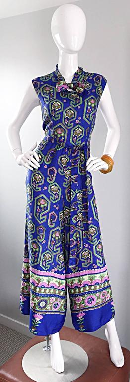 Phenomenal 70s wide palazzo leg jumpsuit! Vibrant blue color with multi color geometric paisley print throughout. Detachable sash belt. Pussycat bow above bust. Pockets at both sides of the waist. Hidden zipper up the back. No fabric tag, but feels