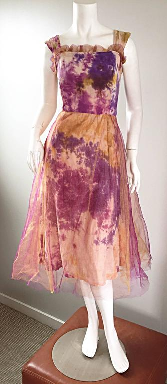 Incredible vintage 1970s tie dye vintage dress! Features purple, tan, blue and orange tie dye print throughout. Bodice is fitted and boned. Full A-Line skirt with two layers of purple and orange tulle overlay. Simply enchanting, and wonderfully