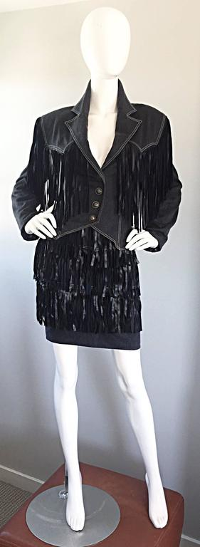 Fantastic and rare vintage PATRICK KELLY denim and leather Western inspired fringed jacket and skirt suit set! Tailored fitted denim jacket with black leather fringe hand-sewn onto the front and back. Perfect high waisted fitted denim skirt, with