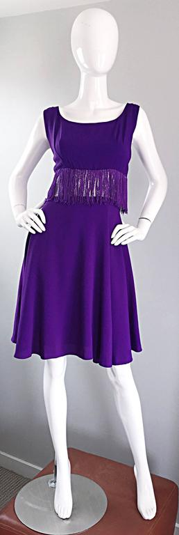 Cutest vintage 1960s purple and silver metallic fringed A - Line dress! Flattering pleats at each bust, with a tailored bodice and full A-Line skirt. Features a silver metallic lurex waistband with purple fringe hand-sewn on top (on the front and