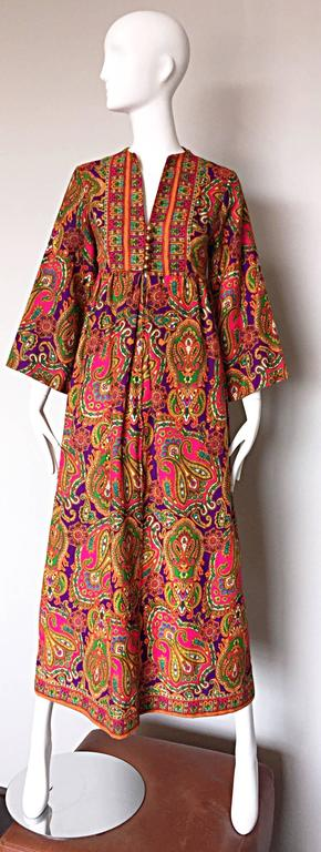 Wonderful vintage 1970s JOSEPH MAGNIN colorful paisley kaftan / maxi dress! Features an allover regal paisley print in pink, purple, green, orange, blue and gold throughout. V-neckline with golden ball buttons up the bodice, with a hidden zipper