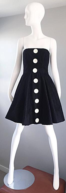 Sensational vintage CHRISTIAN LACROIX Couture black and white dress! Features a black silk and cotton netting throughout. Five oversized mock buttons up the front. Built in interior support to keep everything in place. Hidden zipper up the back with