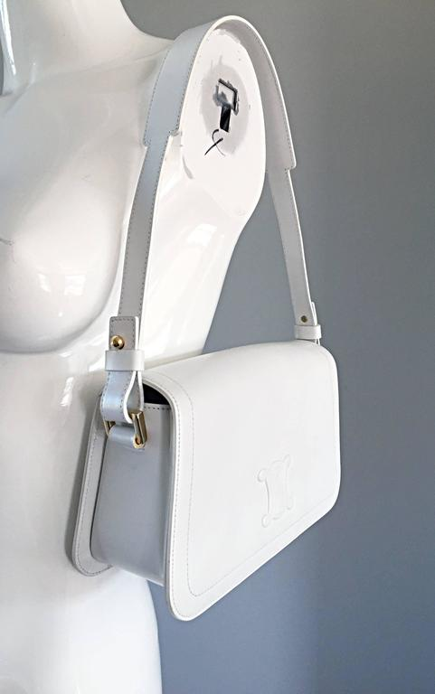 Chic brand new (never used) vintage CELINE stark white leather structured handbag! Features soft structured leather, with the embossed Celine logo on the front flap. Strap can be removed to use as a clutch. Shoulder strap features a wider top in