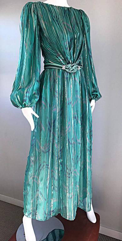Gorgeous vintage late 70s DIANE DICKINSON silk gown! Features vibrant hues of greens, pink, purple, blue and gold prints throughout. Full Flowy bishop sleeves, with emerald green jeweled button closures at the cuffs. Detachable corded green silk