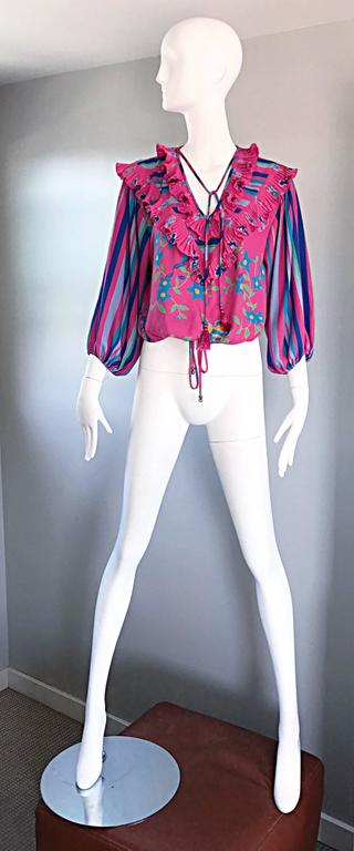 Chic vintage DIANE FREIS / FRES pink, blue, green, marigold, and lavender bohemian top! Features Allover prints of flowers and stripes. Ruffle details at bust and shoulders. Tassels at bust feature beads and fringe at ends, and can be tied or let