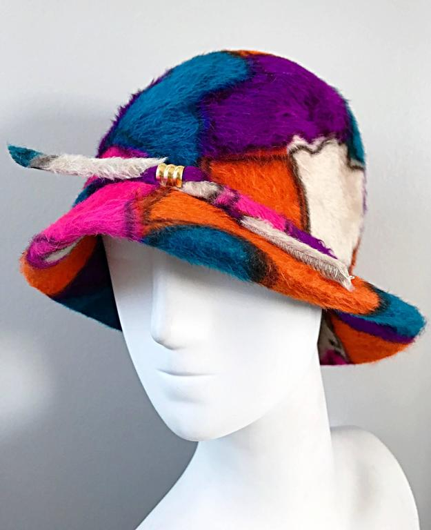Rare 1960s YVES SAINT LAURENT color block abstract printed cloche hat! Features vibrant hues of purple, orange, fuchsia pink, blue and ivory throughout. Band across the entire hat, with a center gold loop. Looks amazing on! Great with jeans, a