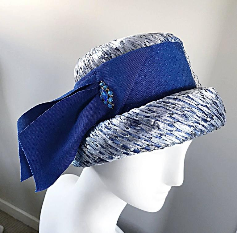 Gorgeous, and brand new with original tags, 1950s BERESFORD blue straw hat! Features light blue straw, with a royal blue silk grosgrain ribbon. Blue rhinestone detail at side. Looks amazing on! Couture quality. In great unworn condition. Will fit a