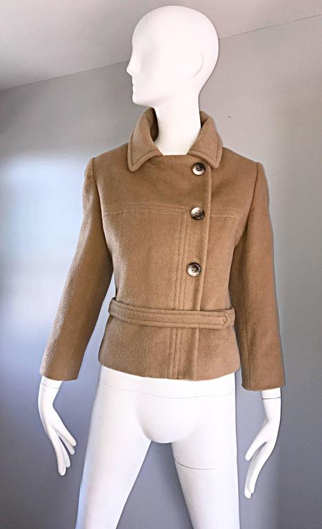 Chic and beautiful 1960s SAKS 5TH AVE perfect camel color cropped wool jacket! Sleek tailored fit, with interesting stitching detail on the front. Attached wrap belt with multiple hidden snaps. Mock horn buttons up the front, with hidden snaps to