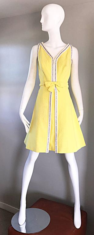 Chic vintage 1960s SEATON ENTERPRISES LTD. Couture canary yellow beaded and rhinestone A-Line dress! Textured yellow cotton rayon blend, with thousands of hand-sewn rhinestones and white beads down the center, and around the collar. Attached bow