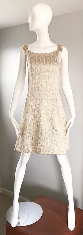 Chic 60s gold metallic silk brocade A-Line dress! Features a gorgeous silk brocade in gold and white gold, with gold metal loops attached to each shoulder. Full metal zipper up the back with hook-and-eye closure. Flattering fitted bodice, with a