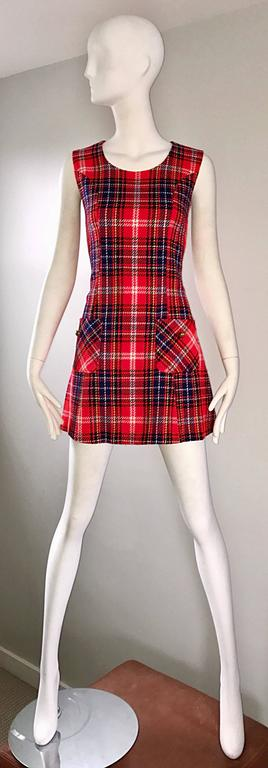 Chic 1960s tartan plaid scooter A-line dress! Features vibrant cherry red, navy blue, and yellow plaid throughout. Pocket at each side of the waist, with a brass gold button on each. Full metal zipper up the back with hook-and-eye closure. Flirty