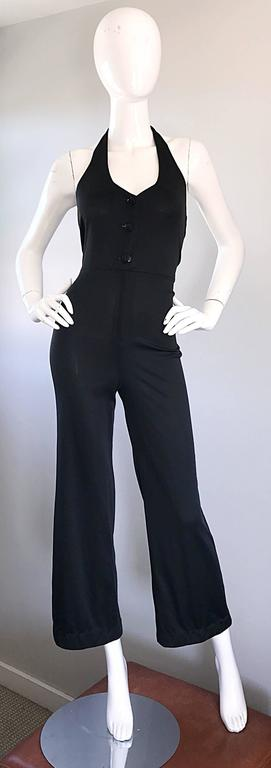 Sexy vintage 70s black jersey halter jumpsuit! Features a tailored bodice that buttons up the front. Hidden zipper at waistband. Nice flare legged / bell bottom. Buttons at back center halterneck. Looks amazing on, and hugs the body in all the right