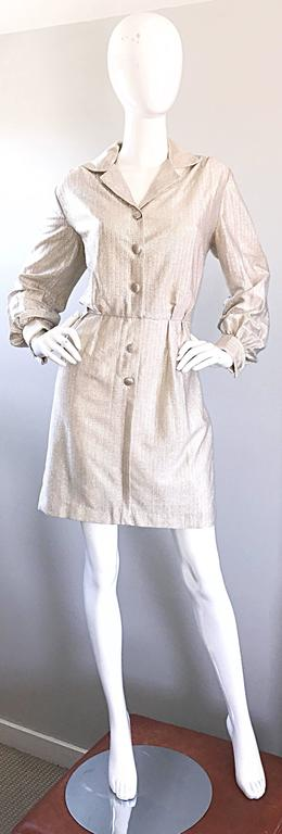 Chic 1970s white gold + silver metallic lurex long sleeve shirt dress! Features fabric covered buttons up the bodice and at each sleeve cuff. Hidden        hook-and-eye closure at front waist. Flattering pleating detail on the waist. Fully lined.