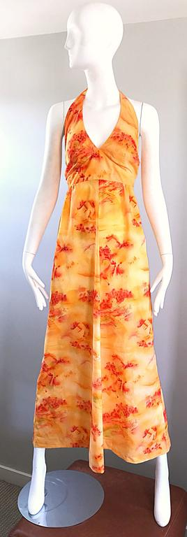 Incredible 1970s Asian themed novelty boho maxi dress! Features a vibrant bright orange, with prints in a brighter orange and red orange throughout. Ties at back top neck with zipper up the skirt. Great with sandals, flats or wedges for day and