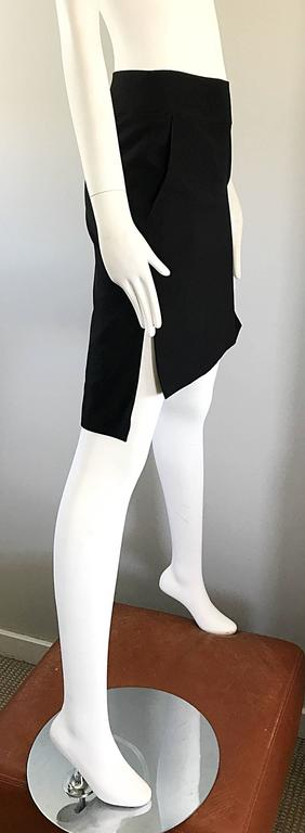 The perfect black early 1990s  vintage hi-low pencil skirt by YVES SAINT LAURENT Rive Gauche YSL ! Features a flattering straight fit, and is shorter in the front, and longer in the back. Pockets at each side of the waist. Hidden zipper up the side